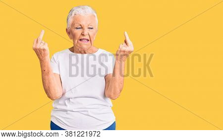 Senior beautiful woman with blue eyes and grey hair wearing casual white tshirt showing middle finger doing fuck you bad expression, provocation and rude attitude. screaming excited