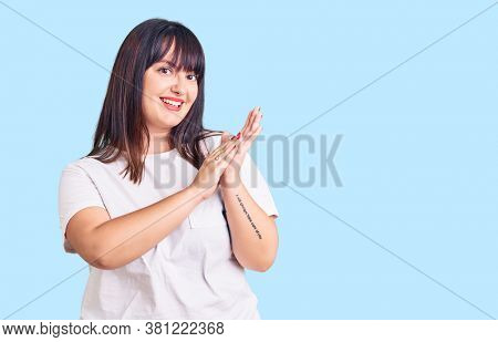 Young plus size woman wearing casual clothes clapping and applauding happy and joyful, smiling proud hands together
