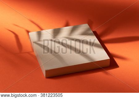 Wooden podium on orange background with the shadow of a palm leaf.