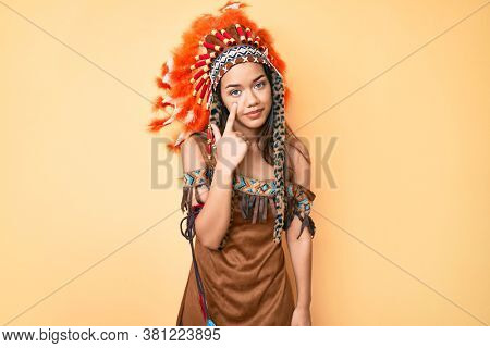 Young beautiful latin woman wearing indian costume pointing to the eye watching you gesture, suspicious expression