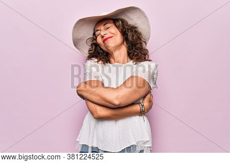Middle age beautiful woman wearing summer t-shirt and hat over isolated pink background hugging oneself happy and positive, smiling confident. Self love and self care