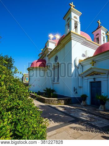 Israel. Capernaum. Orthodox monastery and church of the Twelve Apostles. Snow-white church building with pink domes and golden crosses. Place of worship and pilgrimage