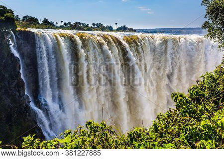 Journey after the wet season. Grand and deep Victoria Falls after the rainy season. Victoria National Park, the Zambezi River. Concept of extreme and photo tourism