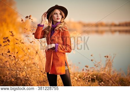 Beautiful young woman posing on riverside in the autumn park. Autumn beauty, fashion.