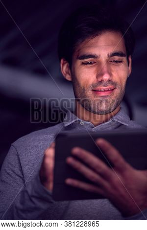 Businessman Working Late Using Digital Tablet With Face Illuminated