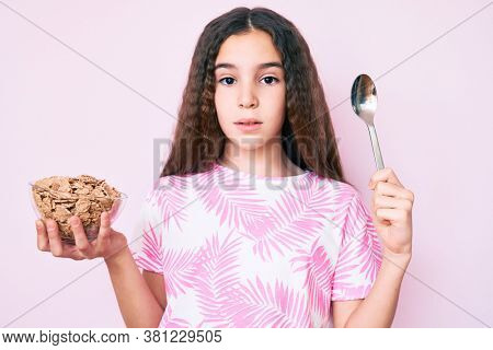 Cute hispanic girl holding cornflakes and spoon relaxed with serious expression on face. simple and natural looking at the camera.