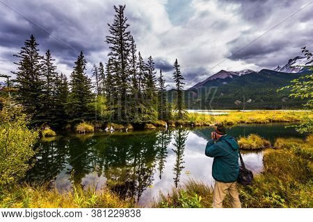 The valley along the Pocahontas road. Man with a photo bag is photographing a beautiful landscape. The lakes, firs and mountains of Canada. Concept of active and photo-tourism