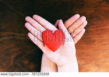 heart in hand for philanthropy concept , woman holding red heart on hands for valentines day or donate help give love warmth take care with wooden background