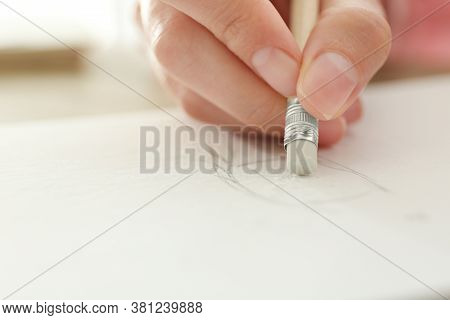 Woman Correcting Picture In Notepad With Pencil Eraser, Closeup