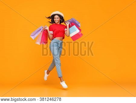 Concept Of Shopping Purchases And Sales Of Happy Young Ethnic Girl With Packages Jumping  On Yellow