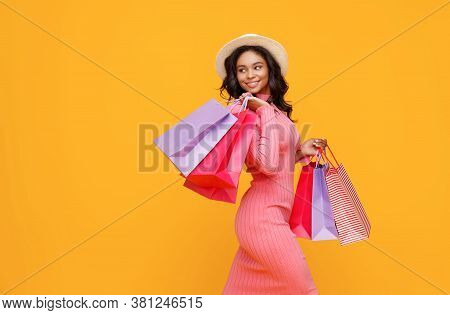 Side View Of Cheerful Ethnic Woman With Paper Bags Smiling And Looking Away Over Shoulder While Walk