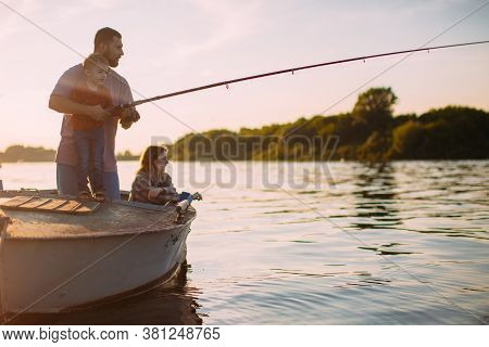 Young Family Fishing On Boat On River In Summertime. Father Teaches Son Fishing. Photo For Blog Abou
