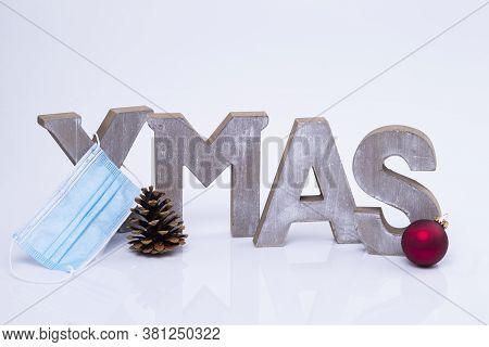 The Photo Shows The Word X-mas Written With Wooden Letters With Protective Mask, Cone And Christmas