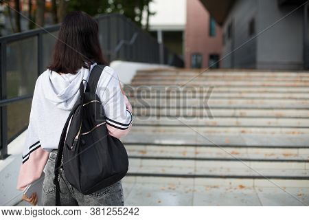 A Female Student With A Black Backpack And A Notebook In Her Hands Stands On The Steps In Front Of T