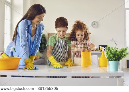 Family Cleaning Room Together And Having Fun. Kids Helping Parent To Do Domestic Chores At Home