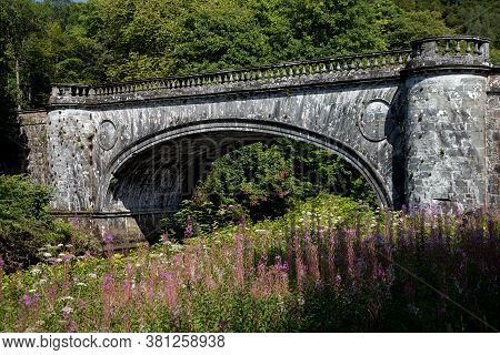 Ancient Stonework Bridge Spanning A Highland River In Scotland