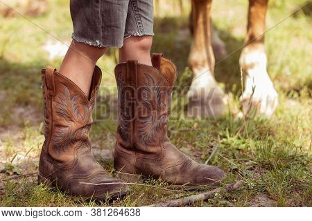 The Childs Legs In Cowboy Boots And The Legs Of The Horse Next To Each Other. Cowboy Concept.