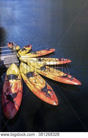 Seven Orange Kayaks On A Dock Placed Radially On A Blue, Vertical