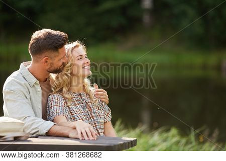 Portrait Of Romantic Adult Couple Embracing While Sitting At Outdoor Table By Lake, Focus On Smiling