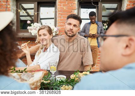 Multi-ethnic Group Of People Enjoying Dinner Outdoors, Focus On Couple Speaking To Friends, Copy Spa