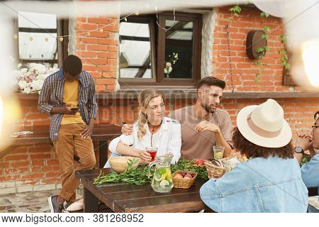 Multi-ethnic Group Of Beautiful Young People Enjoying Dinner Outdoors In Sunlight While Sitting At W