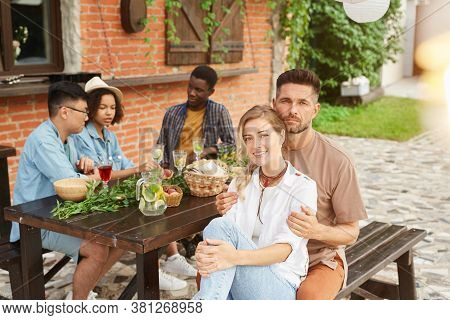 Multi-ethnic Group Of Beautiful Young People Enjoying Dinner Outdoors In Sunlight, Focus On Smiling