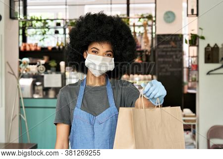 African American Hipster Waitress Wearing Face Mask And Gloves Holding Takeaway Food Order In Hands