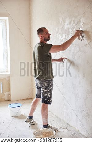 Master Is Applying White Putty On Wall And Smearing By Special Knife In Room Of Renovating Apartment