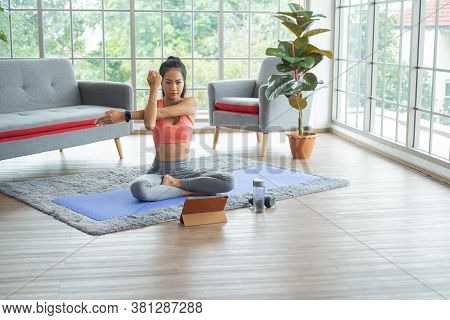 Training At Home. Young Asian Woman Doing Body Stretching While Online Tutorial On Tablet.