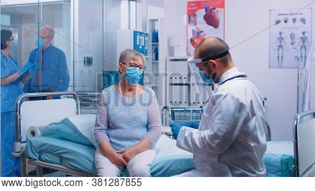 Physician Discussing Lungs Diagnostic Of Retired Old Woman Who Sits On Hospital Bed In Modern Privat