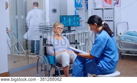 Elderly Patient With Walking Disabilities In Wheelchair Seeking Medical Advice In Recovery Clinic Or