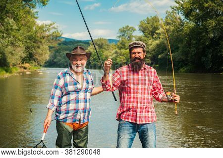 Activity And Hobby. Set Up Rod With Hook Line Sinker. Two Male Friends Dressed In Shirts Fishing Tog