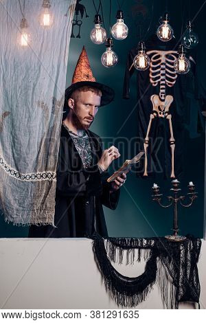 Halloween Witch With A Carved Pumpkin And Magic Lights In A Dark Forest. Halloween Background. Jack-