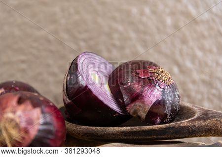 Varieties Of Onions Cut In Halves On Wooden Board