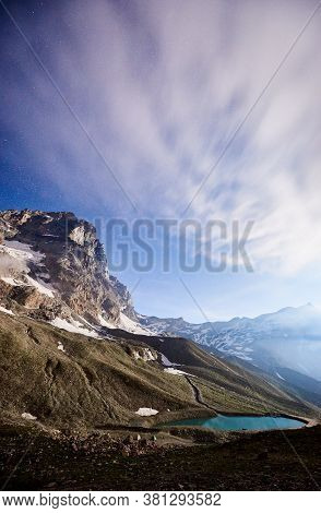 Stunning View Of Majestic Mountains And Blue Lake Under Night Foggy Sky. Beautiful Mountain Landscap