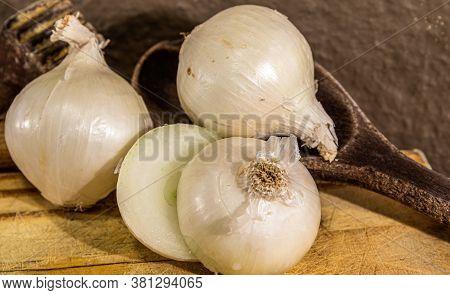 Tubers Of Onions (allium Cepa) Cut In Halves On Wooden Board