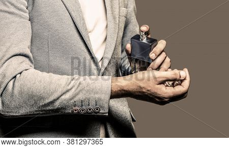 Man Holding Up Bottle Of Perfume. Fashion Cologne Bottle. Man Perfume, Fragrance. Masculine Perfume.