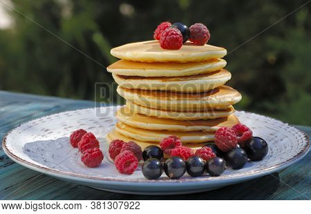 Pancakes. A Stack Of Pancakes On A White Plate Garnished With Raspberries And Black Currants. Food B