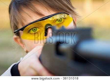 A young girl with a gun for trap shooting and shooting glasses aiming at a target poster