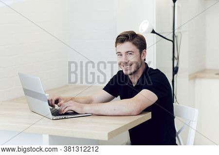 Smiling Young Caucasian Man Working At Home On Laptop Sitting At Desk. Work At A Distance During Qua
