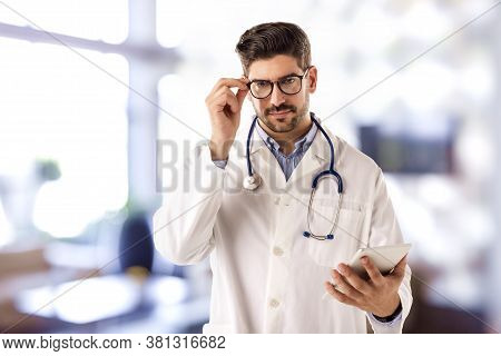 Shot Of Male Doctor Using Digital Tablet While Standing In The Doctor's Office