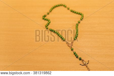 Rosary And Green Catholic Crucifix On Wooden Background