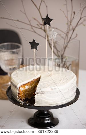 Closeup Of Delicious Carrot Cake Coated With White Cream. Shiny Stars On Top Of A Homemade White Bir