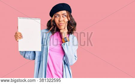 Young beautiful mixed race woman wearing artist look with beret holding notebook serious face thinking about question with hand on chin, thoughtful about confusing idea