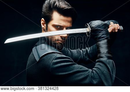 Warrior Man Posing With A Sword Ready To Stab Enemy Isolated On Black Background