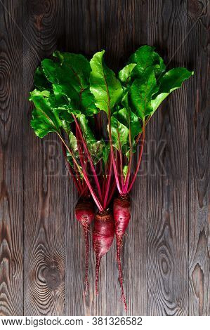 Raw Beets With Green Tops On A Dark Wooden Background. Eco Food, Rustic Style. Top View, Vertical Or