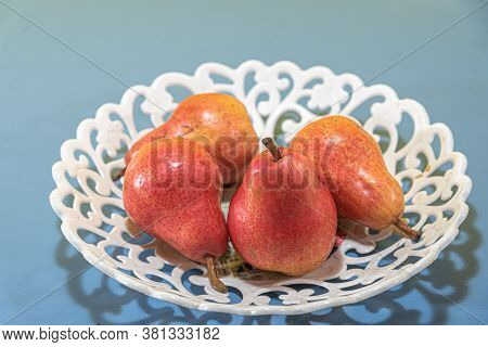 Pear Fruits (pyrus Comunis L.) Variety Red On White Tray And Blue Background