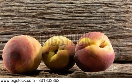 Peach Fruits (prunus Persica) In Natura On A Woody Background