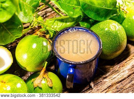 Passion Fruit Juice Served In A Blue Metal Mug And Fresh Fruits Around It