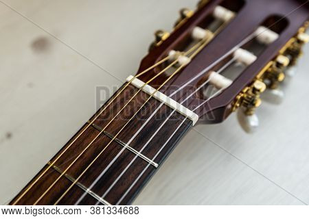 Detail Of The Neck And Pegs Of A Spanish Guitar. Brown Classical Guitar With Detail Of Guitar String